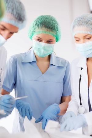 pinzas: asistencia sanitaria y médica - joven grupo de médicos haciendo la operación
