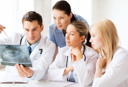 radiology: healthcare, medical and radiology concept - group of doctors looking at x-ray