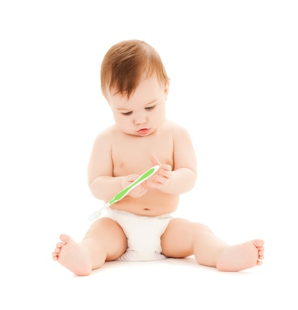 brushing: bright picture of curious baby brushing teeth. Stock Photo