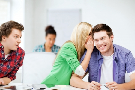 secret: education concept - group of students gossiping at school Stock Photo