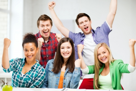 university admission: education concept - happy team of students holding hands up at school