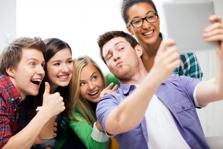 technology concept - group of students making picture with tablet pc photo