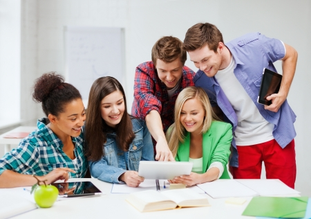application university: education concept - smiling students looking at tablet pc at school Stock Photo