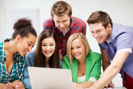 friendly people: education and internet concept - group of international students looking at laptop at school