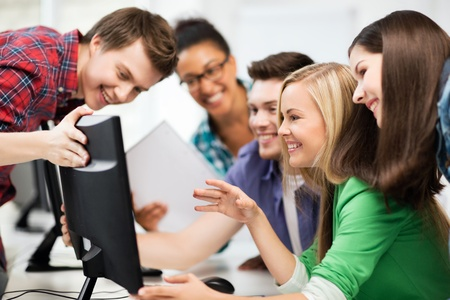 scholar: education concept - students looking at computer monitor at school Stock Photo
