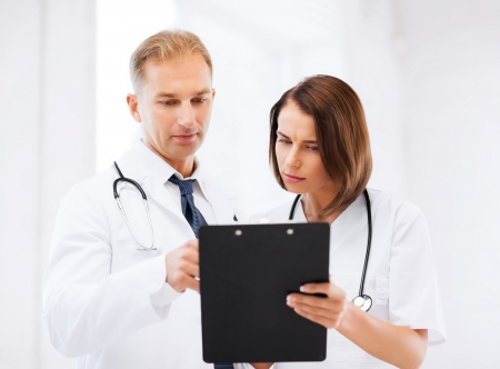 doctor writing: healthcare and medical concept - two doctors discussing diagnosis Stock Photo