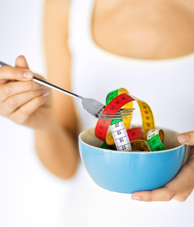 fat and slim: sport and diet concept - woman hands holding bowl with measuring tape Stock Photo