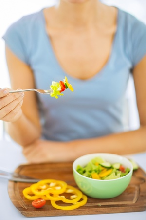 healthy food and kitchen concept - woman hand holding fork with vegetables photo
