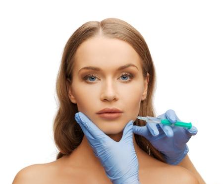 cosmetische chirurgie concept - vrouw gezicht en schoonheidsspecialiste handen met spuit