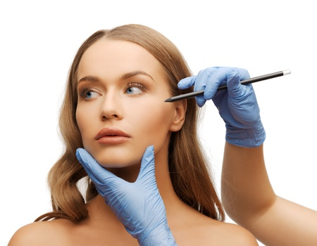 cosmetic surgery concept - woman face and beautician hands with pencil photo