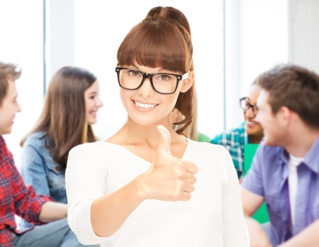 human thumb: education concept - smiling student girl in glasses showing thumbs up at school