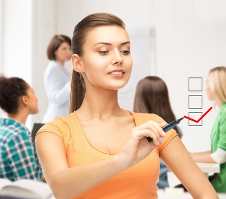 people voting: education and technology concept - student drawing checkmark on virtual screen Stock Photo