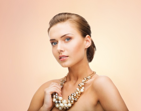 bijouterie: beauty and jewelery concept - beautiful woman wearing statement necklace with pearls
