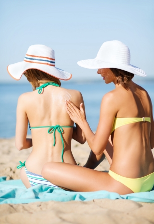 skin protection: summer holidays and vacation - girls applying sun protection cream on the beach