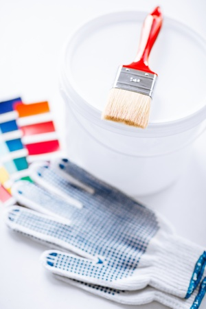 interior design and home renovation concept - paintbrush, paint pot, gloves and pantone samples photo
