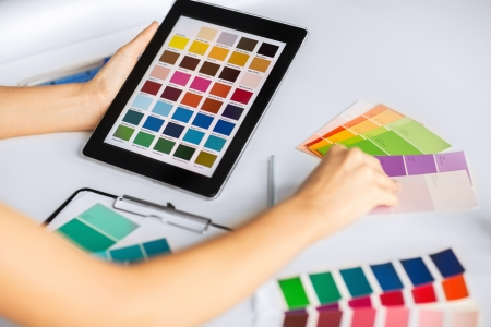 decorator: interior design, renovation and technology concept - woman working with color samples for selection