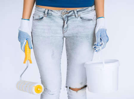 refurbish: interior design and home renovation concept - woman with roller and paint pot