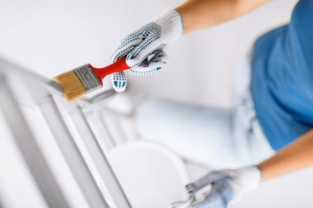 インテリア デザインとホーム改修コンセプト - 絵筆と塗料ポットを持つ女性