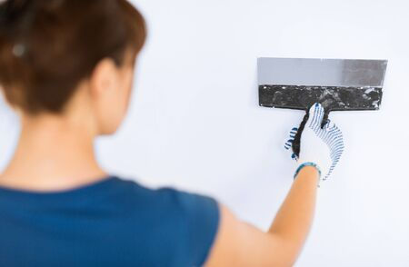 caulking: interior design and home renovation concept - woman plastering the wall with trowel Stock Photo