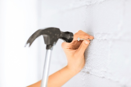 architecture and home renovation concept - architect hammering nail in wall photo