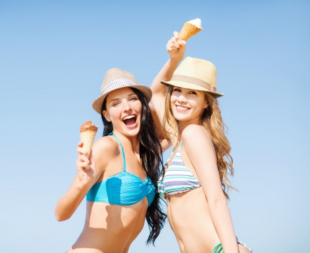summer holidays and vacation concept - girls in bikini with ice cream on the beach photo