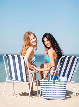 chaise longue: summer holidays and vacation - girls in bikinis sunbathing on the beach chairs Stock Photo