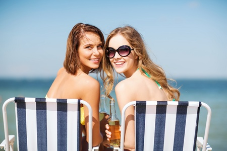summer holidays and vacation - girls in bikinis with drinks on the beach chairs photo
