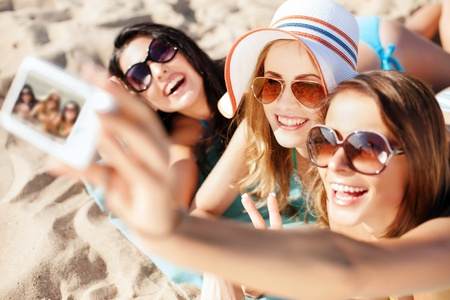 girls: summer holidays, technology and beach concept - girls making self portrait on the beach