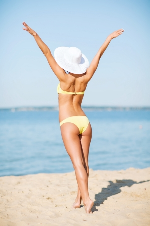 hands behind back: summer holidays, vacation and beach concept - girl in bikini posing on the beach Stock Photo