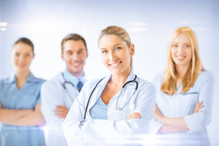 healthcare and medicine concept - female doctor in front of medical group photo