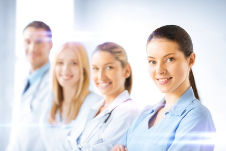 healthcare: healthcare and medicine concept - female doctor in front of medical group