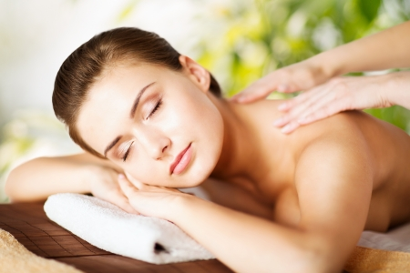 woman in spa: beauty and spa concept - woman in spa salon getting massage