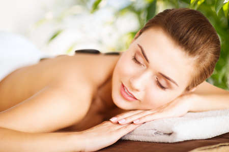 beauty and holidays concept - woman in spa salon with hot stones photo