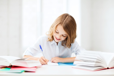youngsters: education and school concept - little student girl studying at school
