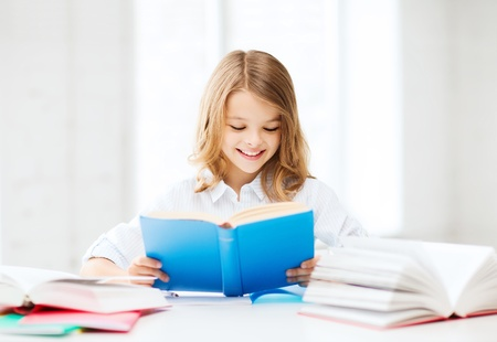 book reading: education and school concept - little student girl studying and reading book at school
