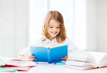 onderwijs en school concept - klein student meisje studeren en het lezen van boeken op school