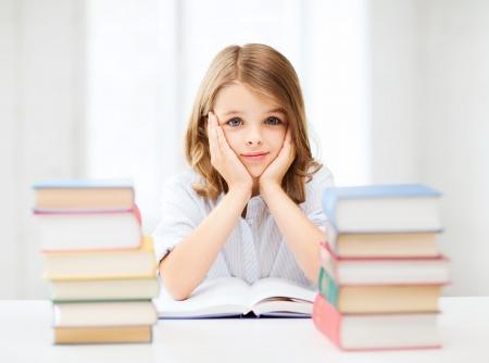 fille triste: l'�ducation et le concept de l'�cole - petite fille �tudiant �tudier et lire des livres � l'�cole