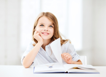 scholars: education and school concept - little student girl studying at school