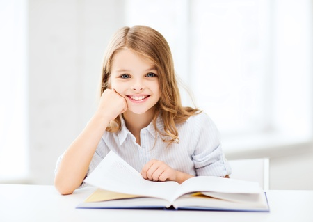 children reading: education and school concept - little student girl studying at school