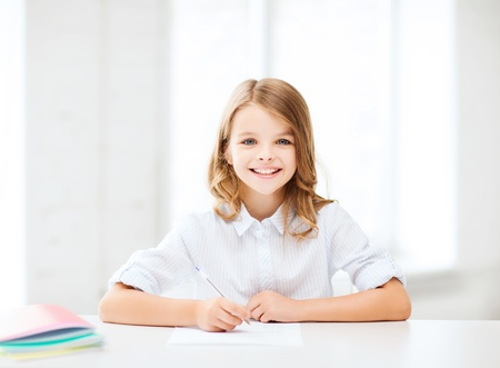 classes: education and school concept - little student girl studying at school
