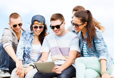 youth culture: summer holidays, teenage and technology concept - group of teenagers looking at tablet pc