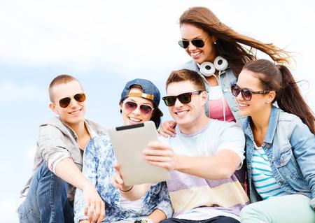 homem: férias de verão, conceito adolescente e tecnologia - grupo de adolescentes que tomam o retrato com tablet pc