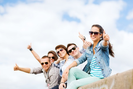 chill out: summer holidays and teenage concept - group of teenagers showing thumbs up