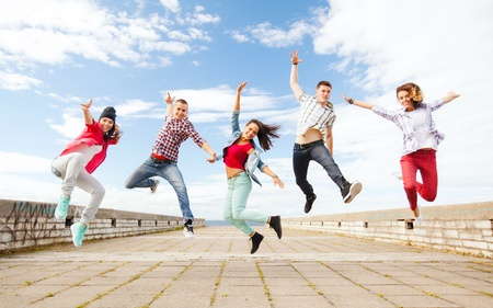 teen dance: summer, sport, dancing and teenage lifestyle concept - group of teenagers jumping Stock Photo