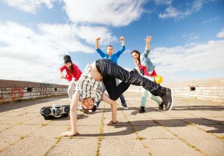 dancing girl: sport, dancing and urban culture concept - group of teenagers dancing
