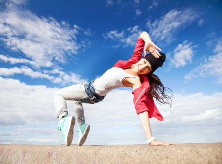 sport, dancing and urban culture concept - beautiful dancing girl in movement photo