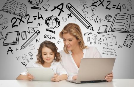 padres e hijos felices: concepto de la educación, la tecnología, internet y la paternidad - niña y la madre con la tableta y el ordenador portátil Foto de archivo
