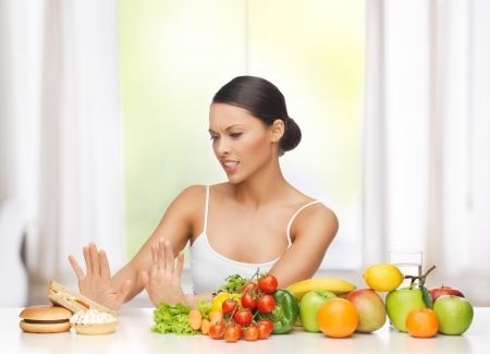 unsatisfied: healthy and junk food concept - woman with fruits rejecting hamburger and cake