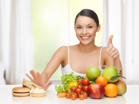 junk: healthy and junk food concept - woman with fruits rejecting hamburger and cake