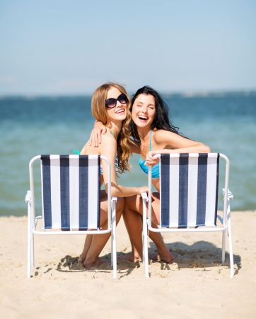 summer holidays and vacation - girls in bikinis sunbathing on the beach chairs Фото со стока